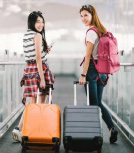 two-girls-traveling-suitcase-airport